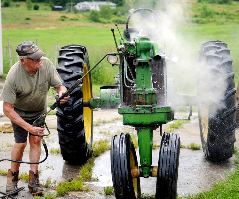 "Jim Norton steam cleans a 1955 John Deere tractor Monday he's rebuilding at his Farmingdale farm. ""Just giving her a bath,"" Norton said of restoring the antique implement, while waiting for the hay to dry for the first cut of the season."