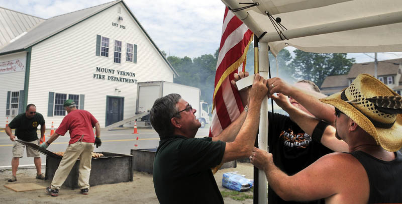 Mount Vernon firefighters John Dearborn, right, Doug Stevens and Dana Dunn hang an American flag Sunday while other volunteers flip racks of chicken barbecuing in scorching heat for the department's annual chicken barbecue in the center of the village. Members of the volunteer company prepare and sell between 500 and 600 meals every year to raise money for the department, Chief Dana Dunn said. This year marks the 40th anniversary of the community cookout, according to Dunn.
