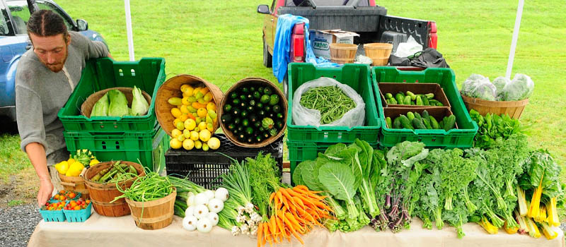 John Strieff sets up the 3 Level Farm booth for the Hallowell Farmers' Market on Tuesday, near the corner of Water and Winthrop Streets in Hallowell. The market is held on Tuesdays from 4 p.m. until dark in the riverfront parking lot, near the city bandstand, which hosts an evening concert series over the summer.