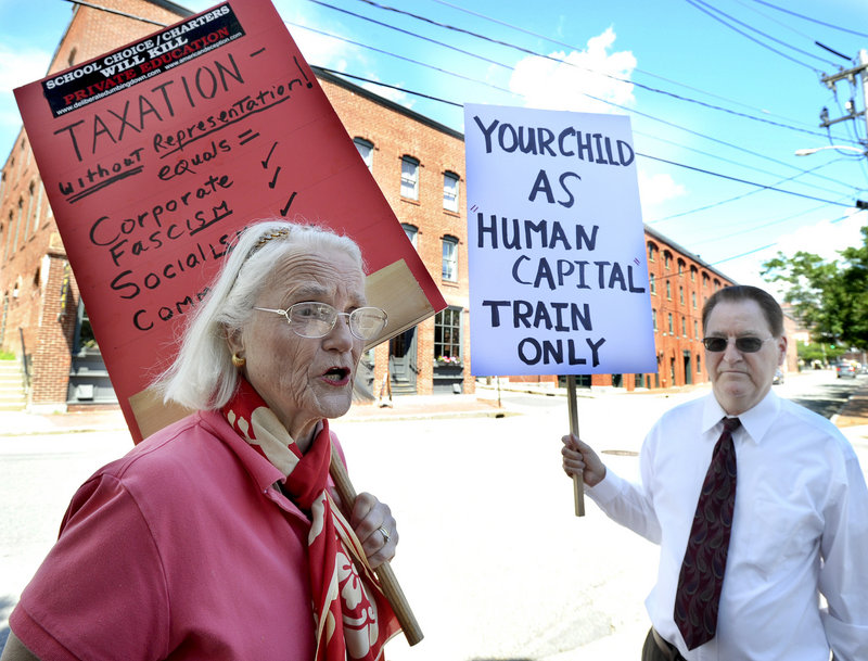 Charlotte Iserbyt of Dresden and Steve Schran of New Gloucester protested outside the Maine Heritage Policy Center luncheon at Baxter Academy in Portland on Wedmnesday, July 31, 2013.