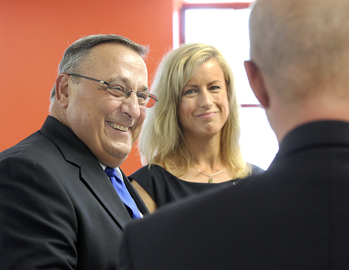 Gov. Paul LePage shares a light moment with Allison Crean Davis, vice chairwoman of the Baxter Academy board, and others during the Maine Heritage Policy Center luncheon at the charter school in Portland on Wednesday.