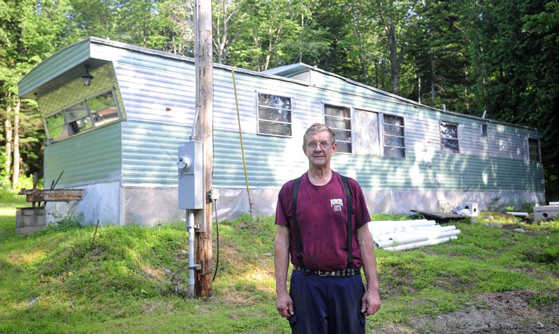 Cliff Risinger stands outside his circa 1978 trailer, at 88 Norridgewock Road in Fairfield on Tuesday. Risinger is applying for a grant that will allow him to fix up his home.