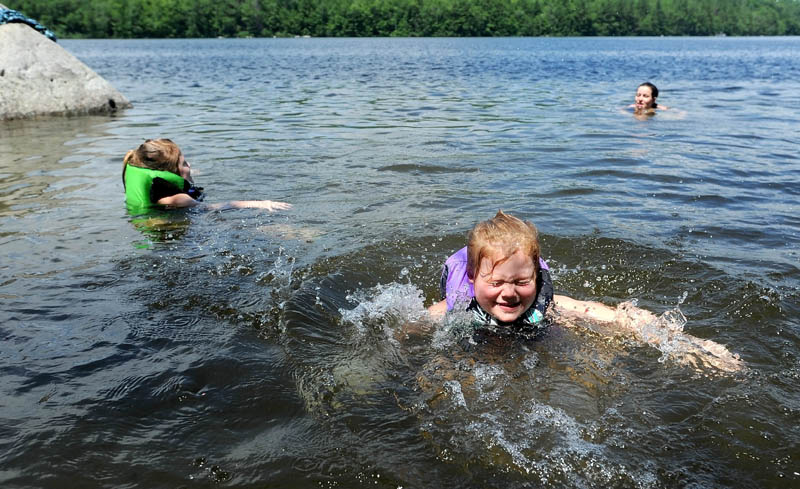 Willow Page, 5, front, sister, Daisy, 6, left, and mother, Mary-Anna, all of Anson, escape the high temperatures in Lake George, on the Canaan and Skowhegan town line, on Friday.