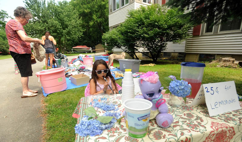 Skylah Rayne Breault-Talon, 7, serenades shoppers with her recorder at her lemonade stand, set up at her mother's yard sale on Silver Street in Waterville on Sunday.