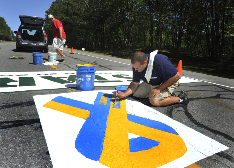 Matt Tobin and Jeremy Gardner paint the starting line on Route 77 in Cape Elizabeth in advance of the upcoming Beach to Beacon road race. Tobin, an employee of Pioneer Athletics, put the finishing touches on painted Boston Strong ribbon in memory of this year's Boston Marathon tragedy.