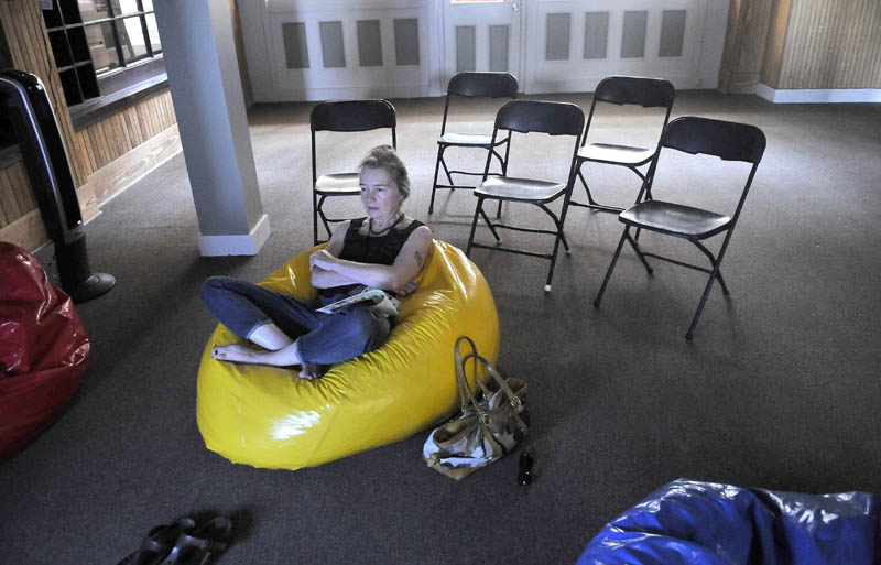 "Karen Young watches a MiffOnEdge presentation of Nam Jun Paik's ""Global Groove"" from a bean bag chair at the old post office in downtown Waterville on Saturday."