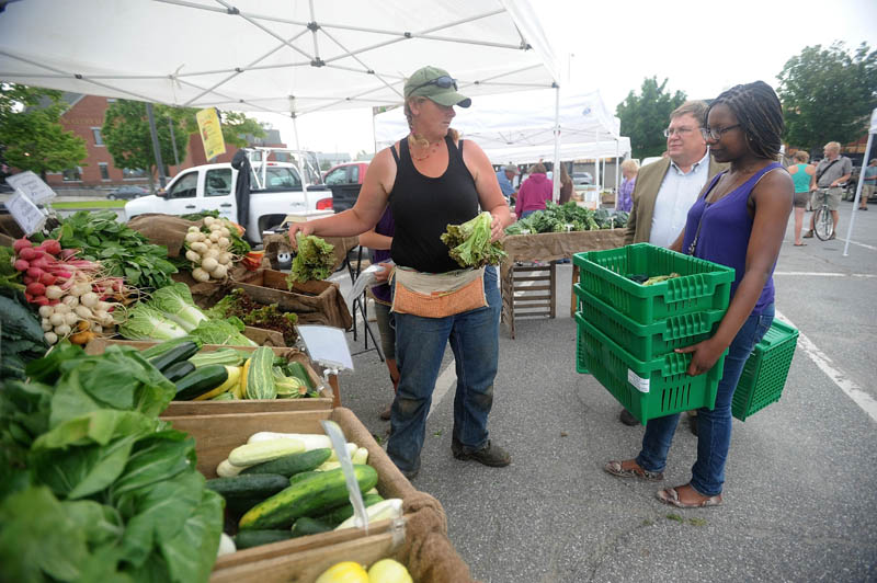 Hanne Teirney, left, with Corerstone and Fail Better Farms, offers organic produce to Noma Moyo, 21, a Colby College junior, right, and Joe Klaus, food services manager at Colby College, at the Waterville Farmers' Market at the Concourse on Thursday. Klaus, along with volunteer students, collect food from the farmer's market for distribution to local pantries.