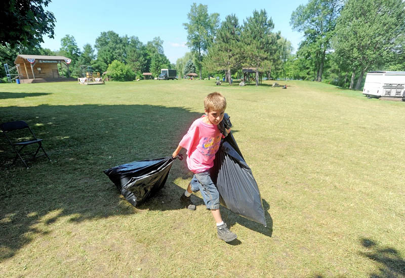 Hunter Desveaux, 12, hauls bags of trash to a waiting truck as he helps clean up after the Winslow Family 4th of July Celebration at Fort Halifax Park in Winslow on Friday.