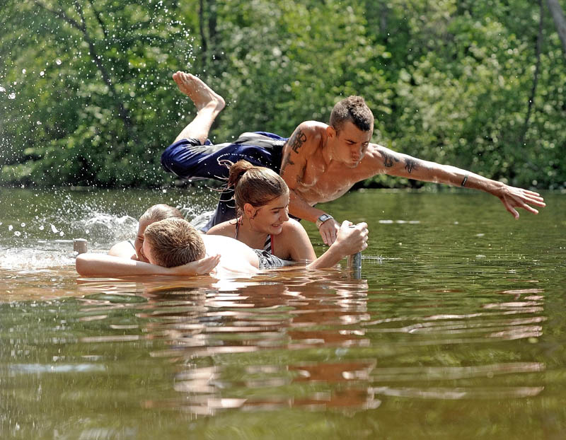 Travis Decato, 20, leaps over his friends, Jennifer Stanphill, 19, right, Joe Andrews, laying on the deck, bottom center, and Samantha Thomas, 21, hidden, in to the Messalonskee Stream in Waterville on Saturday.