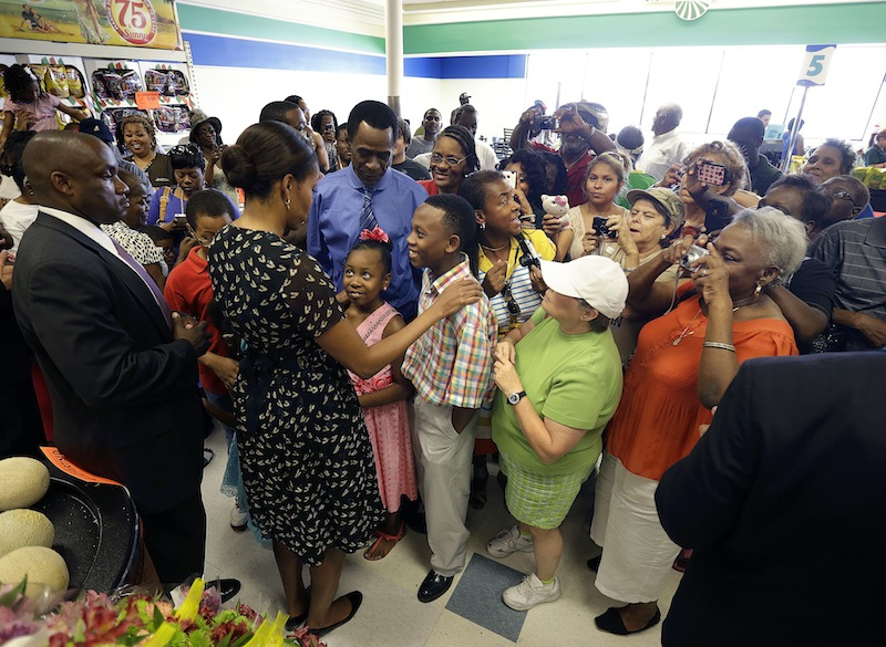 """First lady Michelle Obama greets customers at Sterling Farms Grocery Store in Marrero, La., Tuesday, July 23, 2013. The store was opened last year by actor Wendell Pierce as part of the """"Alliance For A Healthier Generation."""" Earlier she spoke about childhood obesity at the annual meeting of the National Council of La Raza. (AP Photo/Gerald Herbert)"""