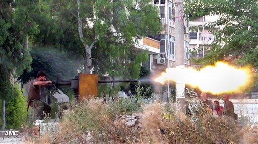 This citizen journalism image provided by Aleppo Media Center AMC, which has been authenticated based on its contents and other AP reporting, shows a Syrian rebel firing a heavy machine gun toward soldiers loyal to Syrian president Bashar Assad, in Aleppo, Syria, on June 20.