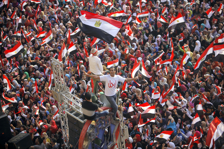 """Opponents of Egypt's Islamist President Mohammed Morsi shout slogans and wave a national flags in Tahrir Square in Cairo, Egypt, on Wednesday. The Arabic says, """"leave."""""""