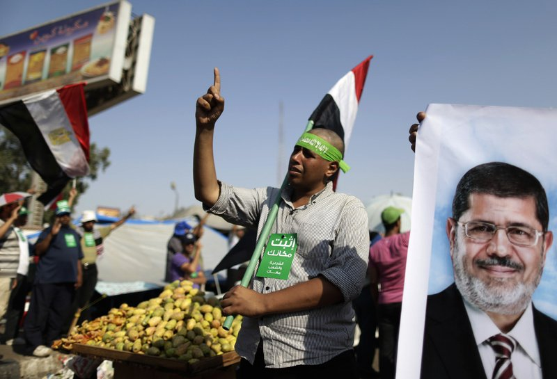 """Supporters of Egypt's Islamist President Mohammed Morsi chant slogans during a rally in Nasser City, Cairo, Egypt, on Wednesday. The green card with Arabic reads, """"stay where you are."""""""