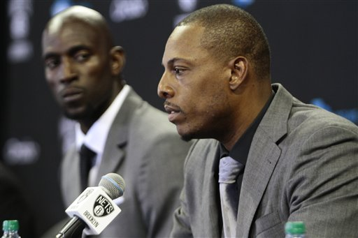 Brooklyn Nets' Kevin Garnett, left, listens as Paul Pierce speaks to the media during a news conference Thursday at Barlcays Center in New York.