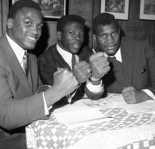 FILE - In this Jan. 3, 1968 file photo, boxer Emile Griffith is flanked by boxers Joe Frazier, left, and Buster Mathis in New York. The International Boxing Hall of Fame says former world champion boxer Emile Griffith has died. He was 75. The hall said Tuesday, July 23, 2013, he died at an extended care facility in Hempstead, N.Y.(AP Photo/File)