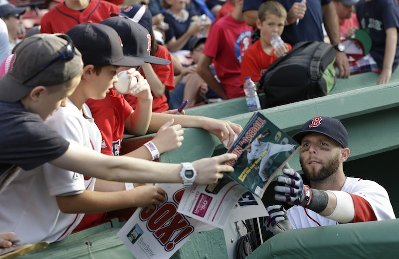 Second baseman Dustin Pedroia signs autographs during the first inning of an interleague baseball game at Fenway Park in Boston on Tuesday, July 2, 2013. (AP Photo/Elise Amendola)