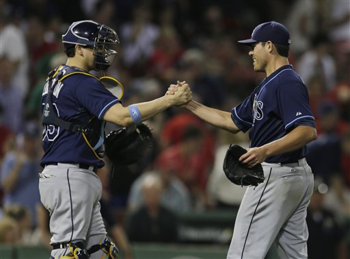 Tampa Bay Rays starting pitcher Matt Moore, right, is congratulated by catcher Jose Lobaton after throwing a complete game and beating the Boston Red Sox in a baseball game at Fenway Park, Monday, July 22, 2013, in Boston. The Rays beat the Red Sox 3-0. (AP Photo/Charles Krupa)
