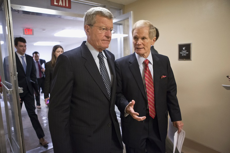 Senate Finance Committee Chairman Sen. Max Baucus, D-Mont., left, and Sen. Bill Nelson, D-Fla., right, join other senators in the rush to the Senate floor on Capitol in Washington, Wednesday, July 10, 2013, for a vote to end debate on the Democrats' plan to restore lower interest rates on student loans one week after Congress' inaction caused those rates to double. The White House and most Senate Democrats favored restoring interest rates on subsidized Stafford loans to 3.4 percent for another year, but lawmakers failed to muster the necessary 60 votes to overcome a procedural hurdle. (AP Photo/J. Scott Applewhite)