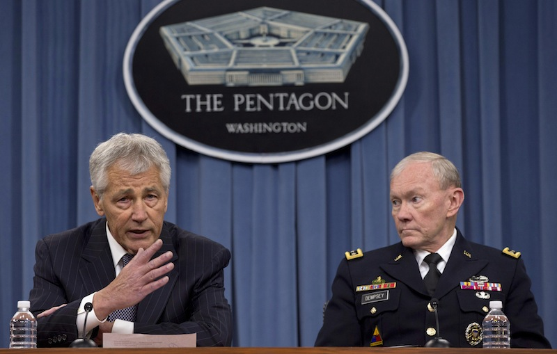 In this May 17, 2013 file photo Defense Secretary Chuck Hagel, left, and Chairman of the Joint Chiefs of Staff, Gen. Martin Dempsey take turns talking to media during a news conference at the Pentagon. Women may be able to begin training as Army Rangers by mid-2015, and as Navy SEALs a year later under broad plans Defense Secretary Chuck Hagel is approving that would slowly bring women into thousands of combat jobs, including those in the country's elite special operations forces, according to details of the plans submitted to Hagel that were obtained by The Associated Press. (AP Photo/Carolyn Kaster, File)