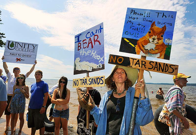 Members and supporters of the environmental advocate group 350.org held a rally at Sebago Lake State Park to protest the potential reversal of the Portland Pipeline that would transport tar-sands oil near Sebago Lake on Saturday. Lynn Stone, of Topsham, carries protest signs made by her niece and nephew at the rally.