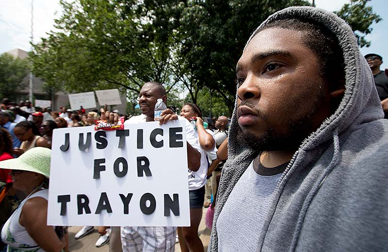 "Ibn Akbar from Boston joins a ""Justice for Trayvon -100 City Vigil"" Saturday as they demonstrate in front of the federal court in Washington."