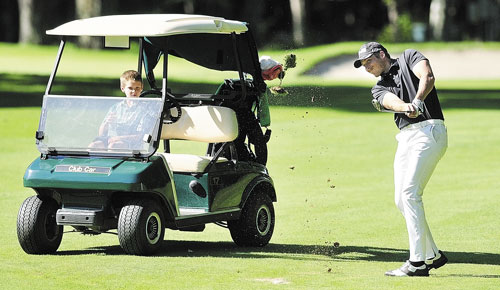 WATCHFUL EYE: Justin Speirs Jr. watches from the cart as his uncle Jesse Speirs drives off the fairway on the back nine during the Charlie's Maine Open Championship on Tuesday at the Augusta Country Club in Manchester. Speirs tied for second with a six under par two day total of 134.
