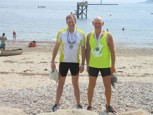 PROUD: Dan Benson, left, and David Grody are shown with their second-place medals after participating in the Blackburn Challenge, a 20-mile race around Cape Ann in Gloucester, Mass.
