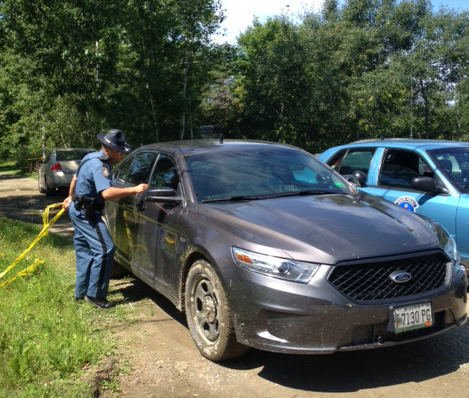 A Maine state trooper speaks with a detective leaving the scene where a dead male was discovered at 24 Main Street in Detroit Thursday morning. The Major Crimes Unit is parked at the mobile home.