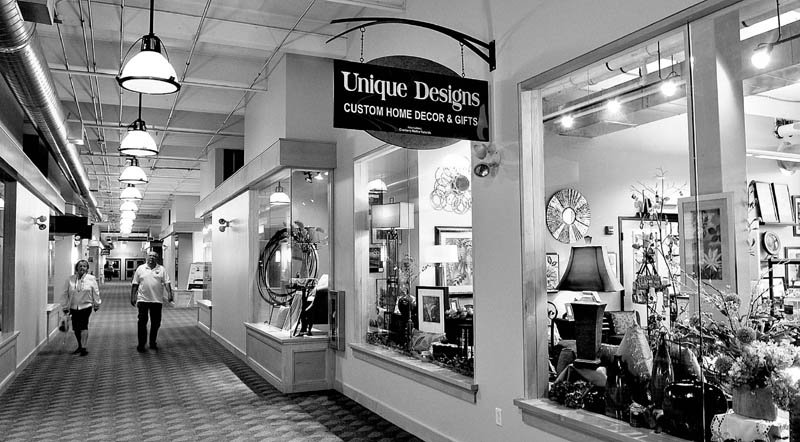 Customers at the Hathaway Creative Center in Waterville walk down the long corridor toward the Unique Designs store after dropping by Maynard's Chocolates.
