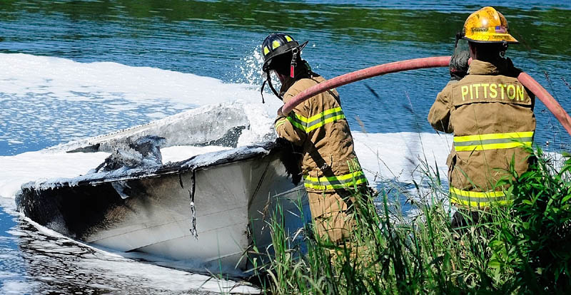 Firefighters on shore spray foam on a burned boat on Friday on the banks of the Kennebec River, near Togus Stream in Pittston.