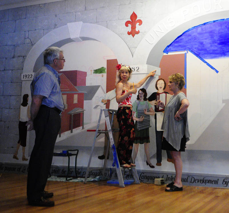 Don White, left, Jane Burke and Corliss Chastain on July 19 talk about what words to put on the side of a column being painted as part of a mural at Le Club Calumet in Augusta.
