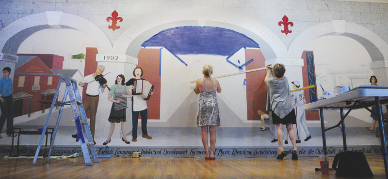 Lisa Lancaster, left, holds a straight edge while Corliss Chastain draws guide lines in pencil as they work on a mural on July 19 at Le Club Calumet in Augusta.