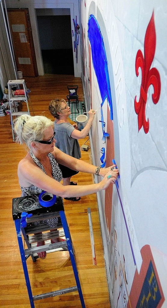 Linda Lancaster, top, paints while Corliss Chastain works on another part of a mural on July 19 at Le Club Calumet in Augusta.