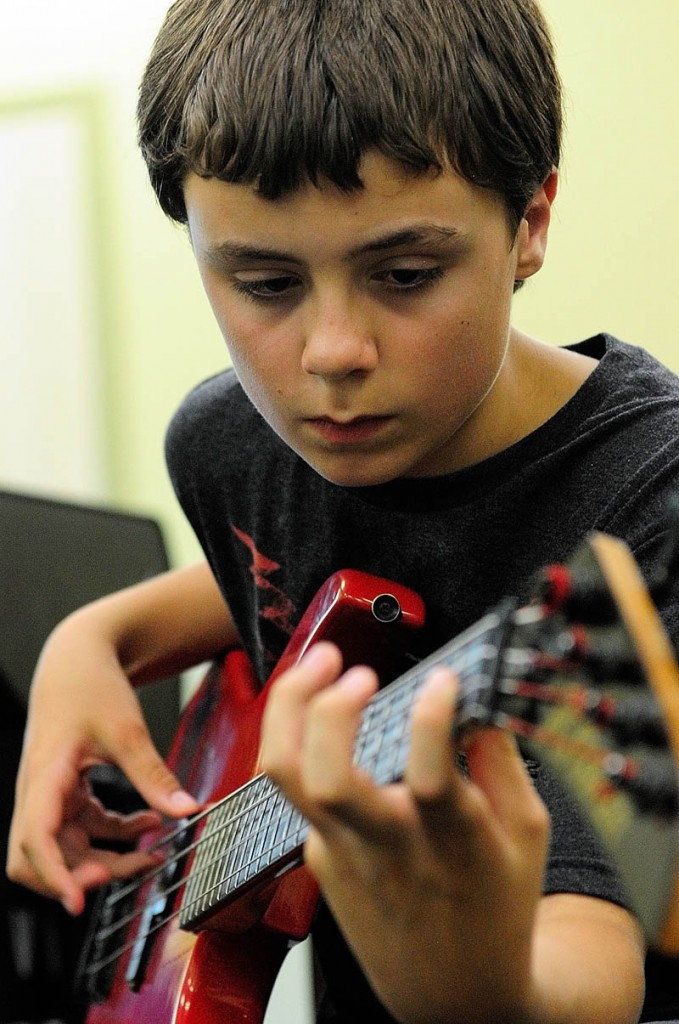 Connor McLean, 12, of Whitefield, plays bass during Rock Camp on Wednesday.