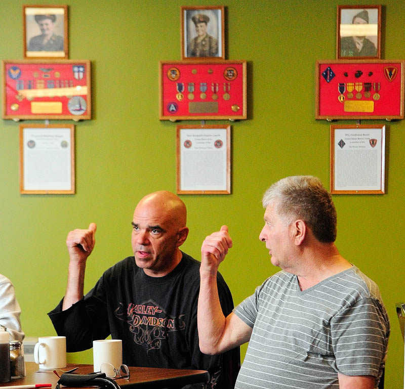 "Thomas ""TJ"" Quinn, left, and Larry Day gesture towardsthe memorial wall display during an interview on Tuesday at TJ's Place, on Route 202 in Monmouth."