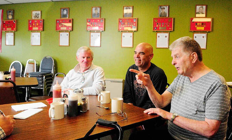"David Harville, left, Thomas ""TJ"" Quinn, center, and Larry Day talk about the memorial wall display during an interview on Tuesday at Quinn's TJ's Place, on Route 202 in Monmouth."