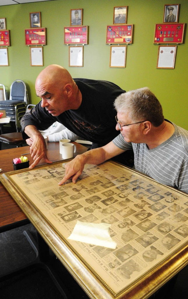 "Thomas ""TJ"" Quinn, left, and Larry Day look at framed newspaper pages showing all the local people killed in World War II, during an interview on Tuesday at TJ's Place, on Route 202 in Monmouth."
