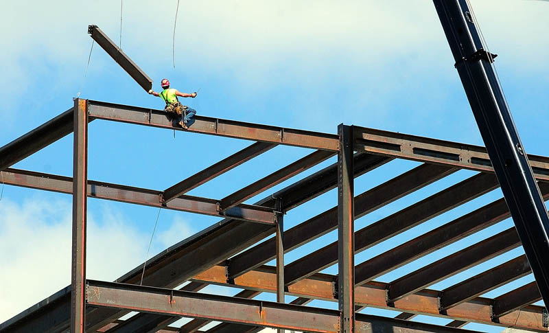 A construction worker reaches for a beam being swung into place by a crane on Thursday at the site of the new Kennebec County Superior Court House being built in Augusta. The new building at the corner of Perham and Winthrop streets is behind the old court house.