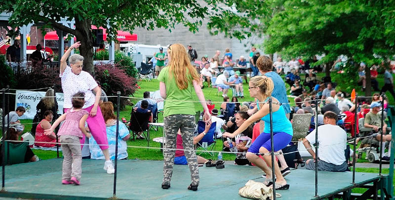 People dance on a stage to the music of the band Borderline Express, which is playing inside the gazebo, on Wednesday during a Waterfront Wednesday concert in Augusta's Waterfront Park. The annual concert series is sponsored by the Augusta Recreation Department., local radio stations B-98.5 and 92 Moose, and Walgreens.