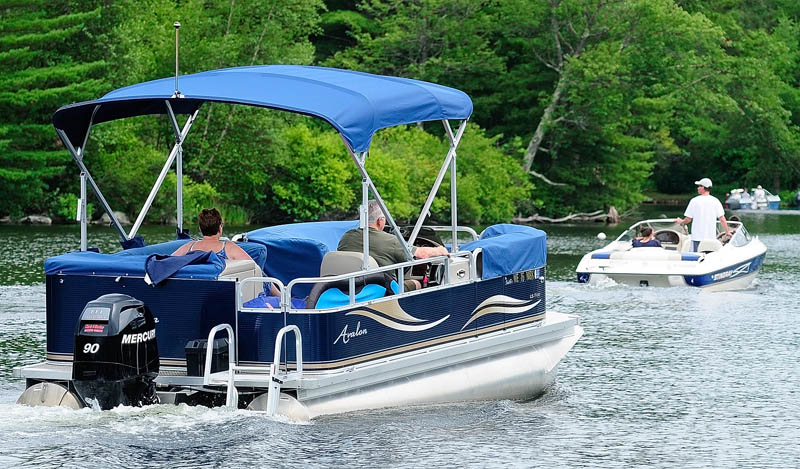 Three boats head out of Belgrade Lakes village on Mill Stream, toward Great Pond, on Thursday in Belgrade.