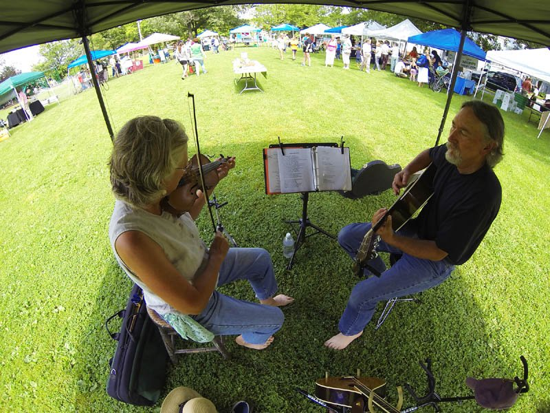 Michele Roy, left, and Will West, performing as Twisted Strings, play under a tent at the Gardiner Common on Wednesday, at the Gardiner Farmers' Market. There are products from 26 vendors at the market, which is held every Wednesday, from 3 to 6 p.m.