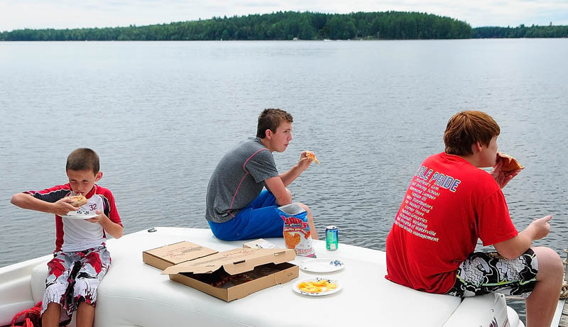 Cousins Daniel McCray, 9 of Augusta, Jordan Martel, 15 of Palm Bay, Fla., and Trevor McCray, 14, of Sidney, eat pizza on the back of a boat docked behind Day's Store on Thursday in Belgrade Lakes. They were taking a break from tubing on Long Pond with their grandfather.