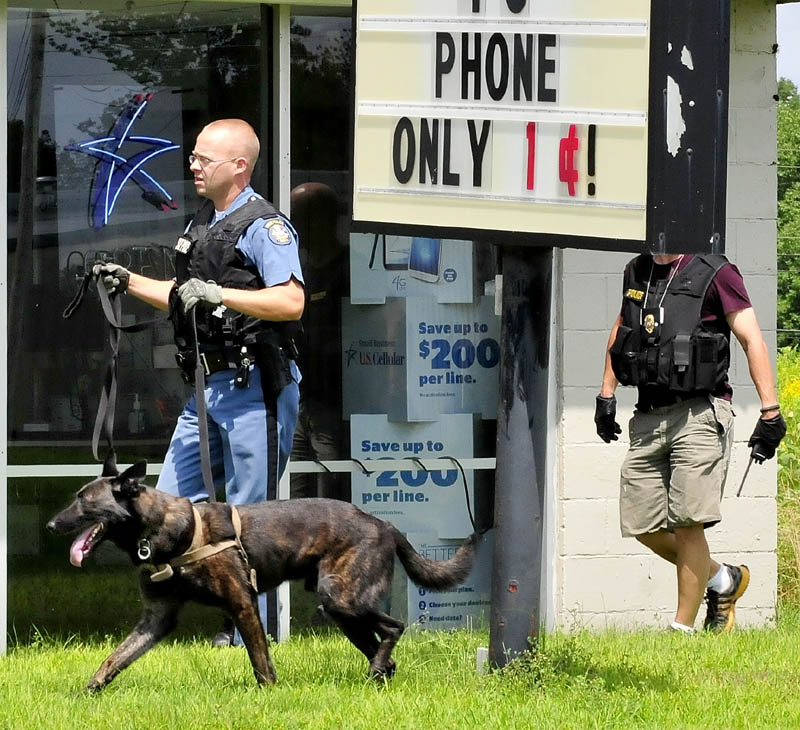 Maine State Police Trooper Scott Dalton, with a tracking dog, and Waterville police officer Bill Bonney search the area off the Armory Road in Waterville after the report that a Little Caesar's restaurant was robbed this afternoon.