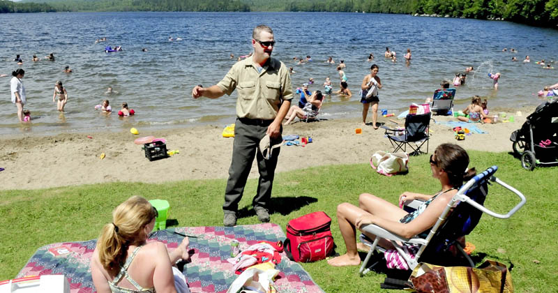 Derek Ellis, the new Lake George Regional Park ranger, speaks with people at one of the crowded beaches on the Canaan side of the lake on July 16.