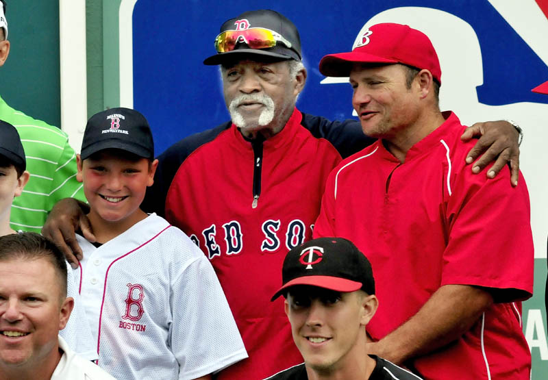 BASEBALL BUDDIES: Former Red Sox pitcher Luis Tiant, center, takes part in a group photograph following a baseball clinic Monday at the Harold Alfond Fenway Park in Oakland.