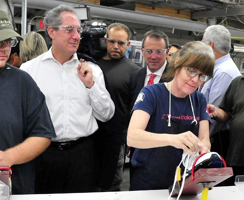 U.S. Trade Representative Michael Froman observes New Balance employee Vicky Dionne lace a new sneaker at the Norridgewock plant today.