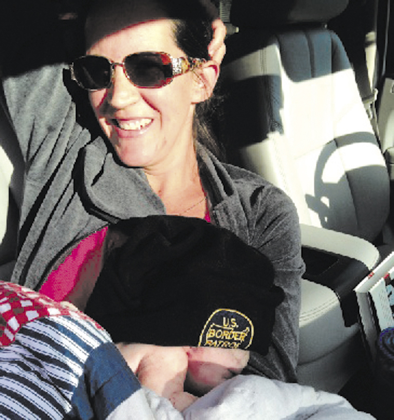 Jill Demanski holds her son, Michael, after giving birth with help from her husband, Chris, in a driveway along Route 104 in Fairfield this morning. The baby is wearing a U.S. Border Patrol hat owned by his father, Chris, who works as an agent for the agency.