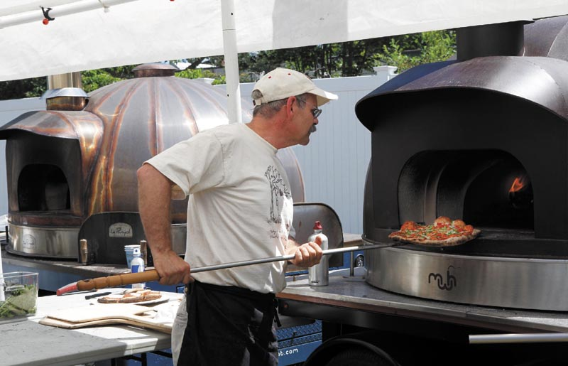 Andy Davis, of Solon, checks on a pizza while baking it in a wood-fired oven during the annual Kneading Conference and Artisan Bread Fair, at the Skowhegan State Fairgrounds, on Saturday. Davis was volunteering at the pizza stand, run by the Maine Grain Alliance. The Le Panyol wood-fired ovens he and fellow volunteers were using were made in Skowhegan by Maine Wood Heat Co. Inc.