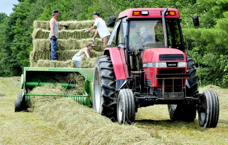 "Charlie Kent, of Benton, drives his tractor as workers stack bales of hay while scrambling to get the crop in on Monday, before the next two days of rain. Kent said his hay crop is behind this year due to the weather. ""Too much rain in the spring and not enough time to dry cut hay this summer,"" Kent said."