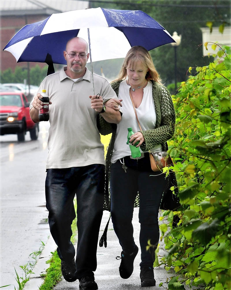 Danny Velez and Hope Stenson sip sodas while walking together under an umbrella during rain on Tuesday.